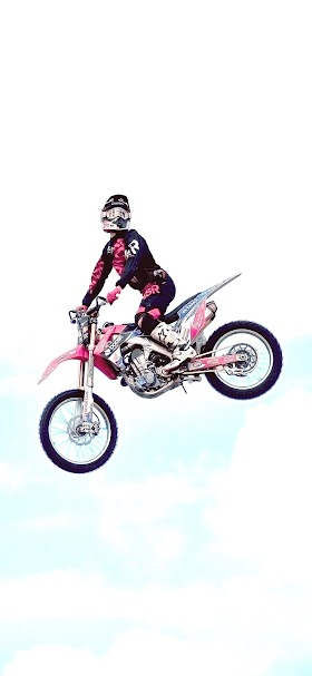 خلفية مؤدي حركات استعراضية يقفز بدراجة نارية