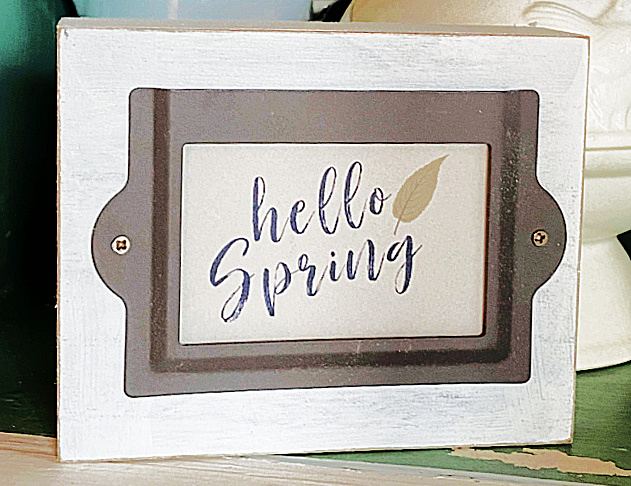 white sign with label and hello spring sign