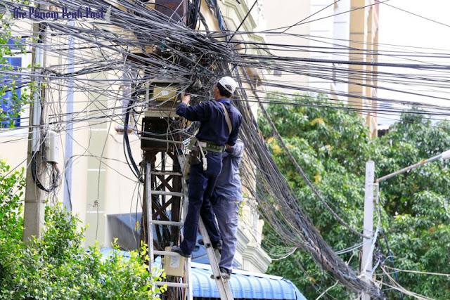 Technicians work to establish a new power connection in central Phnom Penh late last week. Heng Chivoan