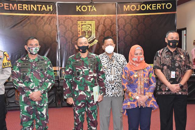 """Mojokerto - majalahglobal.com : Kunjungan kerja yang dilakukan rombongan Kasgartap III/Surabaya Brigjen TNI (Mar) Purwadi M.T.r ( Han) ke Balai Kota Mojokerto disambut hangat oleh Komandan Korem 082/ CPYJ Kolonel Inf M.Dariyanto bersama Forum Komunikasi Pimpinan Daerah (Forkopimda) Kota Mojokerto. Jumat (28/8/2020).  Kunjungan Kasgartap III/Surabaya tersebut bertujuan untuk mempererat komunikasi antar instansi pemerintahan, sekaligus memantapkan kedisiplinan prajurit TNI di Kabupaten Mojokerto. Dalam kunjungan kerja tersebut Kasgartap III/Surabaya menyampaikan, """"TNI akan terus menjalin komunikasi dengan pemerintah daerah karena sinergi antara TNI dengan pemerintah daerah sangat penting untuk membangun daerah ke arah yang lebih baik"""". Pada kesempatan ini Kasgartap juga mengucapkan terima kasih kepada Walikota Mojokerto yang telah menghibahkan tanah seluas 3.438 M² yang terletak di Dusun Kemasan Desa. Blooto Kec. Prajurit Kulon Kota. Mojokerto yang nantinya akan dibangun Markas Komado Sub Kogartap Mojokerto.  Ditempat yang sama, Komandan Korem 082/CPYJ Kolonel Inf M.Dariyanto mengaku senang dan berterima kasih dengan kunjungan yang dilakukan Kasgartap III/Surabaya beserta rombongan ke Kota Mojokerto. """" Selain sebagai bentuk sinergi yang baik, kunjungan kerja Kasgartap III/Surabaya ini juga bisa meningkatkan komunikasi antar institusi Pemerintah Daerah dengan TNI. Terutama seperti saat ini, sinergitas TNI, Pemda dan komponen bangsa lain sangat diperlukan dalam rangka memutus penyebaran Virus Covid-19."""" ungkap Danrem.   Selanjutnya Kasgartap beserta rombongan meninjau Lokasi tanah hibah tersebut di Dusun Kemasan Desa Blooto Kec. Prajurit Kulon Kota. Mojokerto dengan didampingi Danrem 082/CPYJ. (Jayak)"""