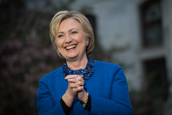image of Hillary Clinton in a blue jacket, smiling and clasping her hands together
