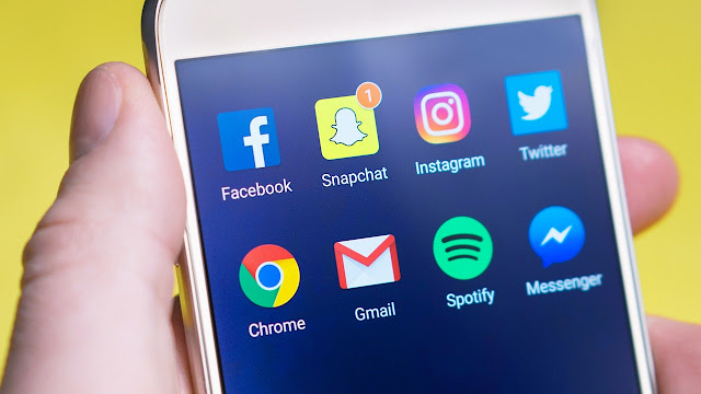 Homem com o celular na mão mostrando as redes sociais