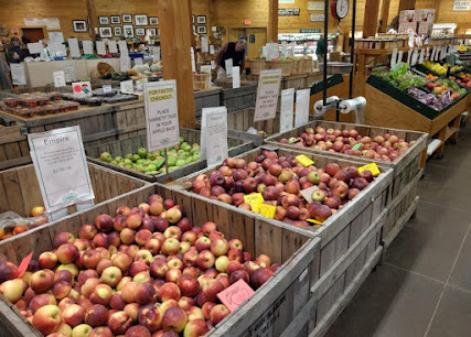 Inside a vast, barn-like store are baskets and wooden bins that hold 17 kinds of apples.