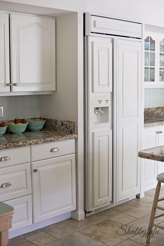 white built in refrigerator with repurposed cabinet doors in a kitchen done over time and on a budget