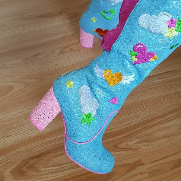 close up wearing pink glitter heeled boots in blue with embroidery