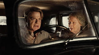 Eddie Izzard and Judi Dench in a 1930s car