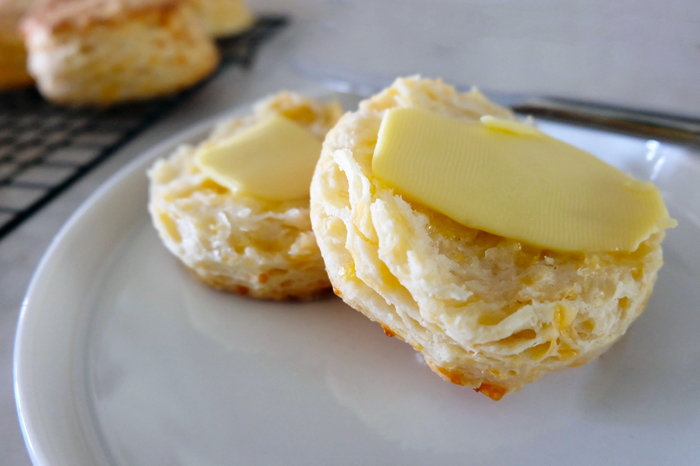 biscuit split on a plate with butter atop