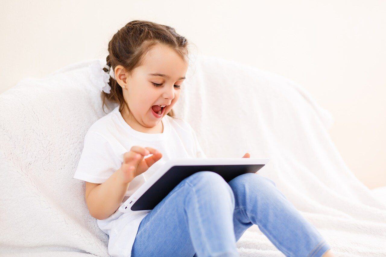 子供が家のソファでタブレットを使っている写真