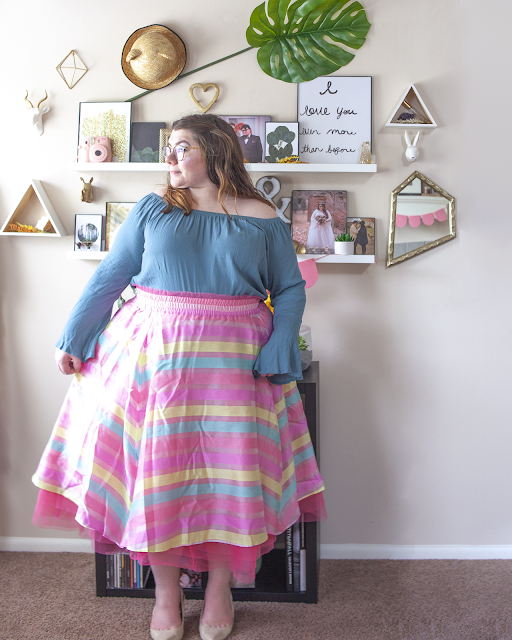 An outfit consisting of a turkish blue off the shoulder blouse with bell sleeves tucked into a pastel pink tulle and organza midi skirt with hot pink, yellow and light blue stripes and beige sling back heels.