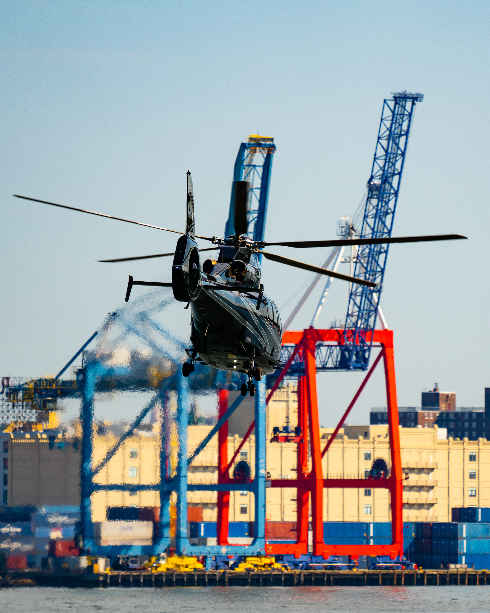 a photo of a black helicopter flying over new york city