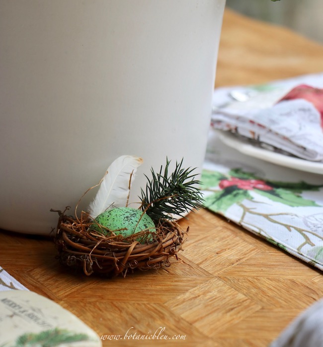 Cardinal Christmas Table Setting centerpiece includes a tiny bird's nest made using a small grapevine wreath, small white feather, and an artificial greenery branch