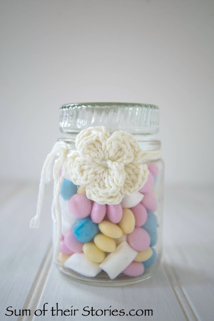 Crochet flowers used for gift wrap sweets in a jar