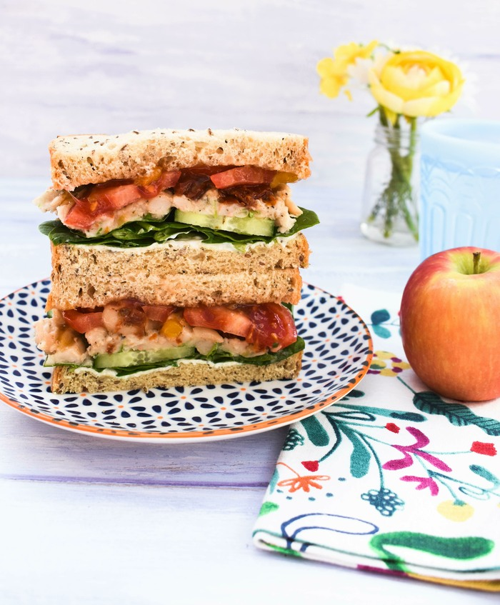 A white bean and tomato sandwich, a red apple and a glass of water