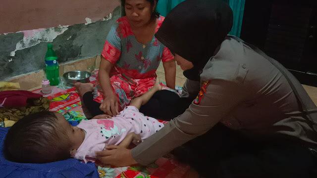 Bripka Tsuraya saat menyambangi bayi menderita hidrocefalus (Foto: Dok Polda NTB)