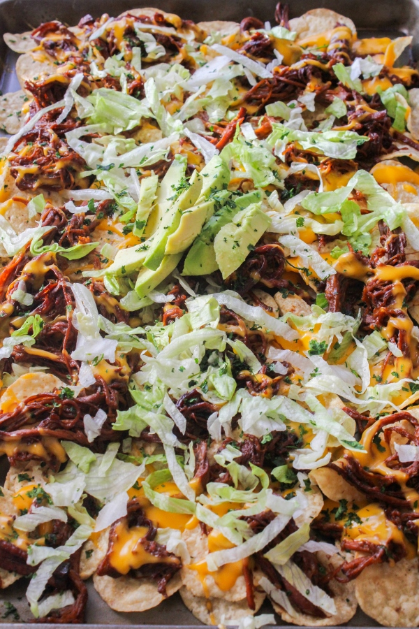 This slow cooked Jamaican Jerk Shredded Beef is cooked in a mouthwatering sweet and spicy sauce until it's tender and falling apart. Serve the shredded beef on top of tortilla chips with your favorite toppings for an epic family meal!