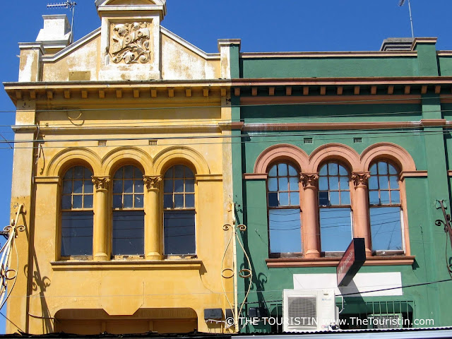 Facades of one yellow and one green Victorian house.