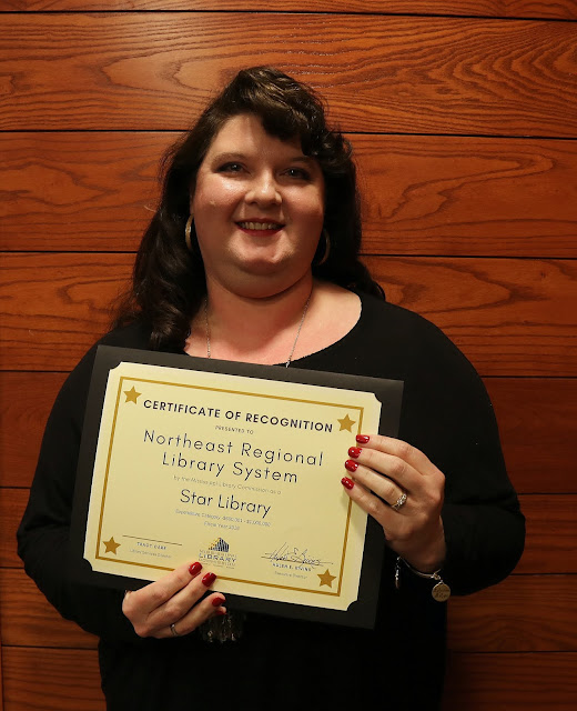 smiling woman holds a certificate of recognition for northeast regional library system