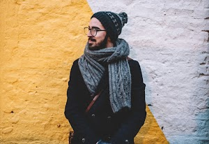 Man in black coat with grey scarf standing on front of white and yellow painted wall