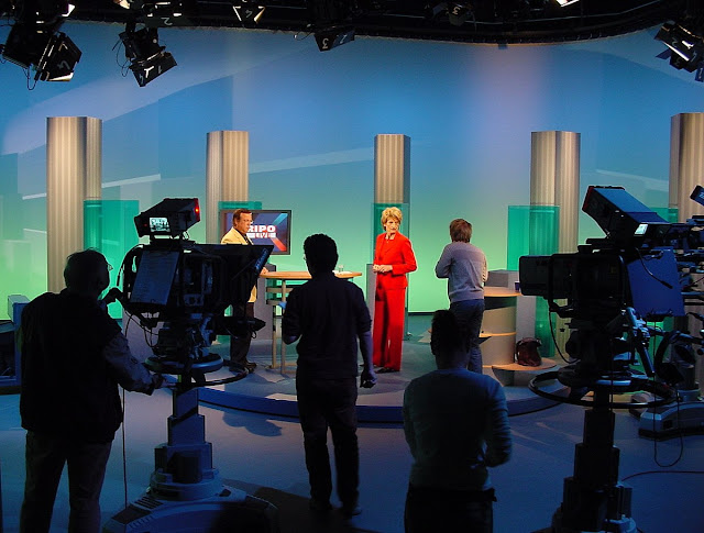 A TV studio set up with cameras and operators in the foreground and the presenters in the background in the on-set studio