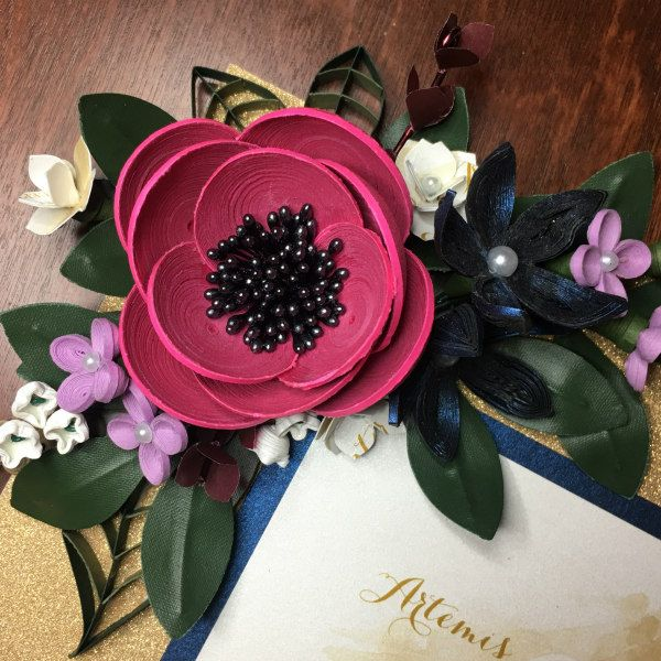 densely quilled colorful flowers decorate a wedding invitation mat