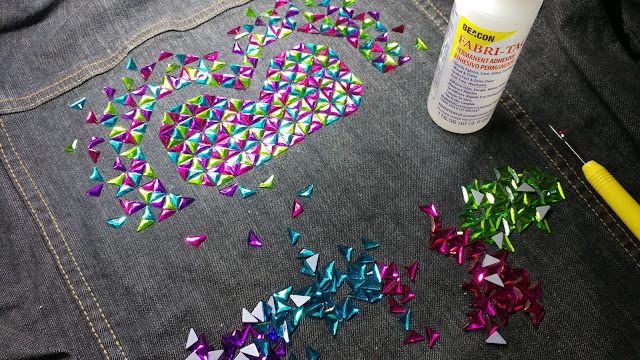 Gluing rhinestones on a denim jacket to make the Exploding Heart quilt