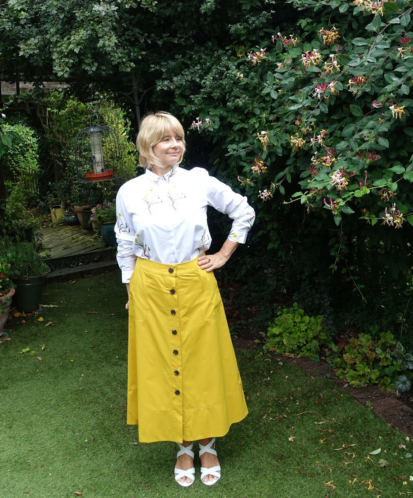 Garden picture of over-50s woman in white patterned shirt and yellow midi skirt