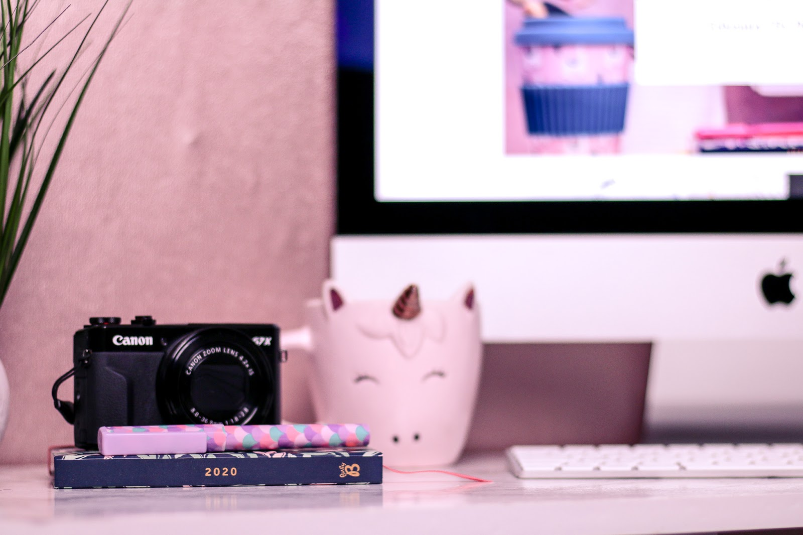 Medium close up of a computer desk with an iMac, black canon a7x camera, pink unicorn mug and 2020 diary on the desk.