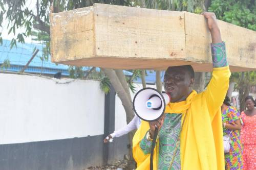 Pastor Carries Coffin, Says God Not Happy With Buhari Govt