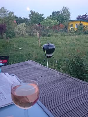 Grill und Weinglas in Abendstimmung.