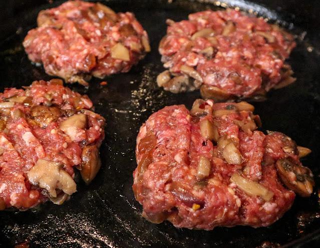 4 raw burger patties sitting on a cast iron pan