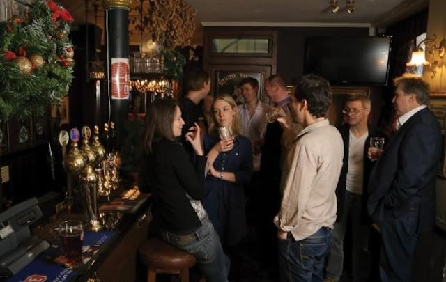Njerët duke pirë në një bar