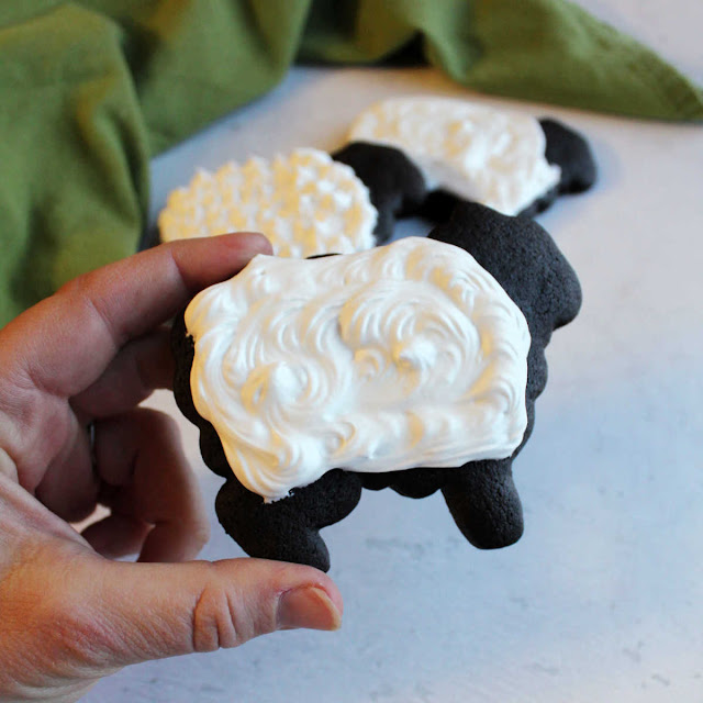 black chocolate sheep cookie with fluffy white royal icing wool