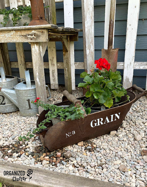 Photo of grain scoop stenciled and filled with potted plants