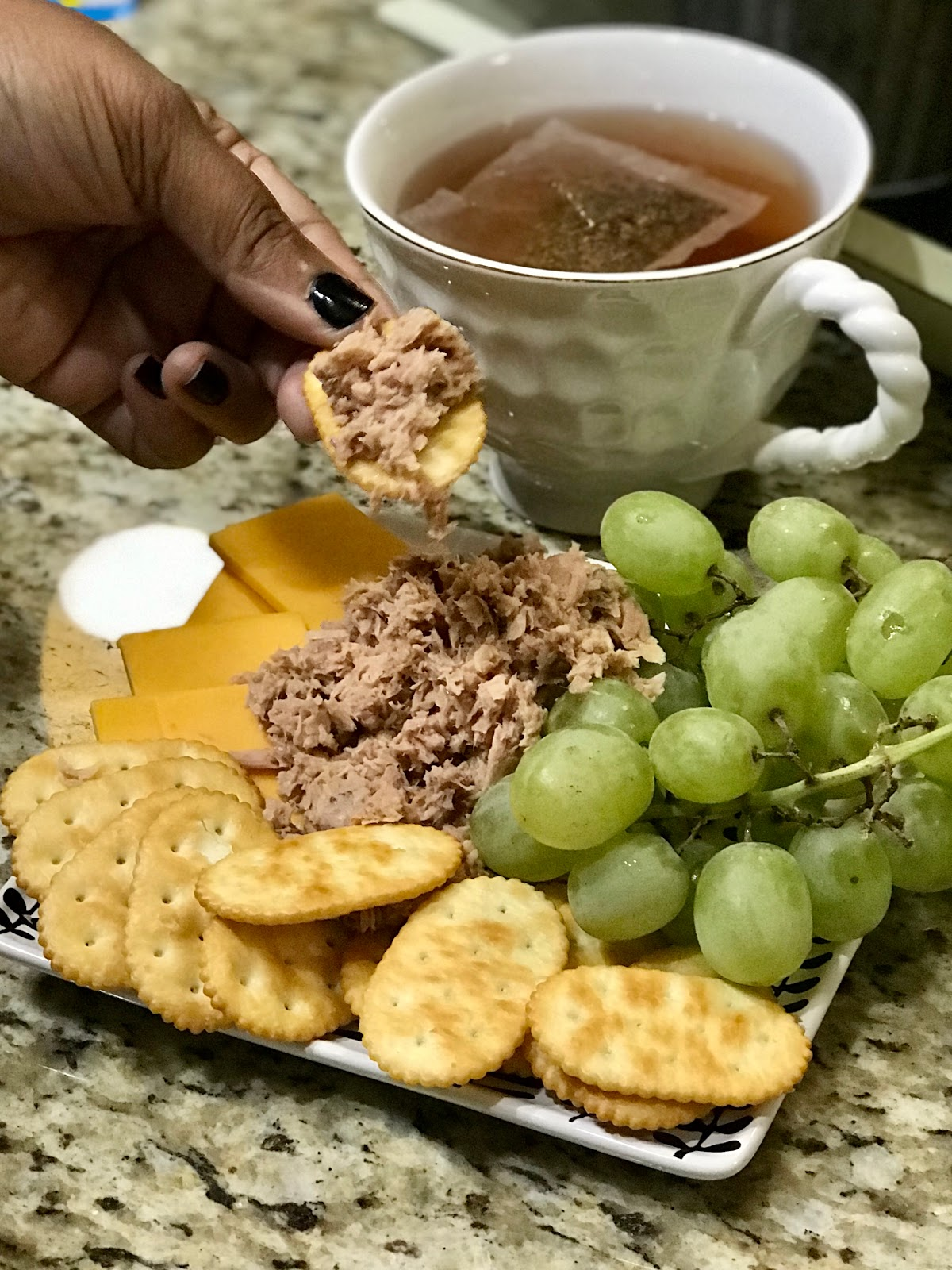 Woman eating tuna with crackers, grapes, sharp cheddar cheese and hot tea