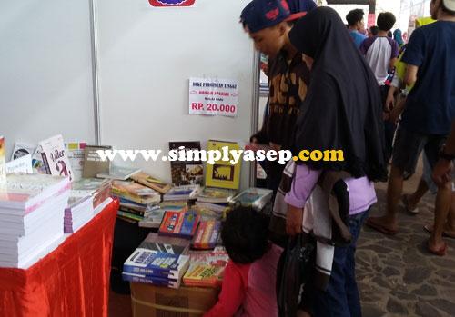 MEMILIH : Pengunjung yang datang bebas memilih buku yang disukai. Ada rabat khusus yang memberi discount hingga 50 persen. Foto Asep Haryono