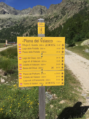 A sign describing places and times to reach them at Piana del Valasco