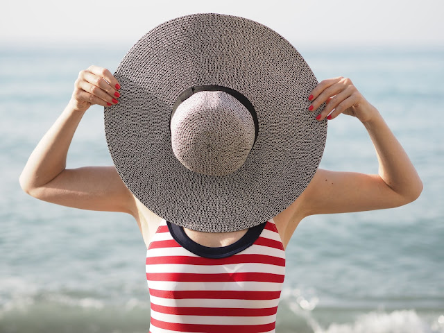 Red striped nautical swimsuit and large floppy straw hat, Nerja beach