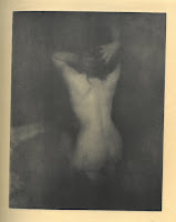 Photogravure of a nude woman kneeling with her back to the camera and her arms clutching her head