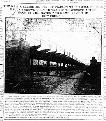 Clipping from a newspaper with a photo (pasted crooked in orginal) with all-caps heading 'The new Wellington Street Viaduct which will be formally thrown open to traffic to-morrow afternoon by the mayor and members of the City Council.' The photo shows a view from ground level of the viaduct overhead, with steel supports and an overhanging sidewalk with railing. There are planks on the ground but the photo from the scanned newspaper is too poor quality to glean other details. The caption below reads: 'The above is a picture of a portion of the new Wellington street viaduct, which will be formally opened for traffic to-morrow afternoon at 2.30 y the mayor and members of teh city council. In the picture is shown the steel work spanning the railway tracks between the two concrete abutments to which the approaches are constructed. Under the steelwork four railway tracks pass within less than 1,000 feet. These were formerly protected by gates, but frequent accidents occurred. Teh character of the ground rendered the construction of the viaduct comparatively easy.  The steel work has a length over all of 522 feet, and is built upon concrete pedestals and concrete abutments. This work was done by the C. P. R.  The balance of the work was constructed by the city, and consists of the pavement over the viaduct, which is made of creasoted wooden blocks laid on tarred planks with sand cushions. The roadway is 30 feet wide. An eight-foot sidewalk runs along the south side. The combined length of the approaches is 645 feet. The filling consists of stone and ashes, and the retaining walls are built of massive masonry. The stone was secured free of cost from the excavations of the Chateau Laurier. Over the approaches there is a steel railing and concrete curb and macadam roadways. The latter two will not be laid until spring. / The estimated cost was $60,000, exclusive of land damages, and the work will be completed within the estimate. The land damages are estimated at $15,000, making the total cost of the work $75,000.'