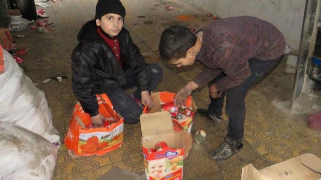 Dua orang anak mengambil persediaan makanan dari sebuah gudang milik kelompok pemberontak di kawasan al-Kalasseh, Aleppo, yang berhasil direbut kembali oleh pasukan pemerintah Suriah.