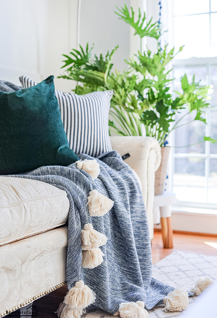 Green velvet pillow on sofa and throw blanket with tassels