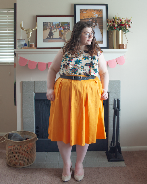 An outfit consisting of a cream dress with vertical ruffles on the front with a jewel toned floral pattern tucked into yellow pleated midi skirt.