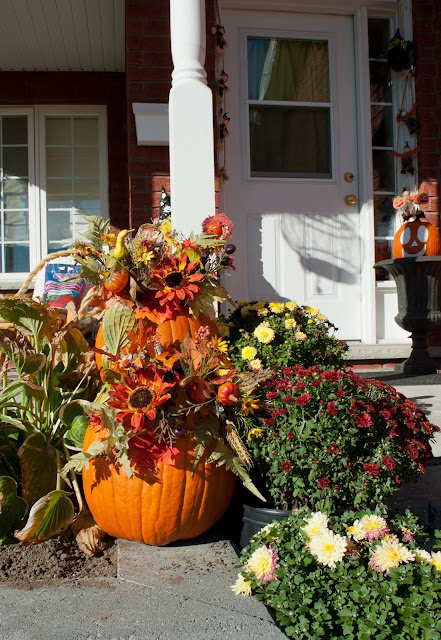 The outdoor decor for fall, Thanksgiving and Halloweed at the front port of a brick home.