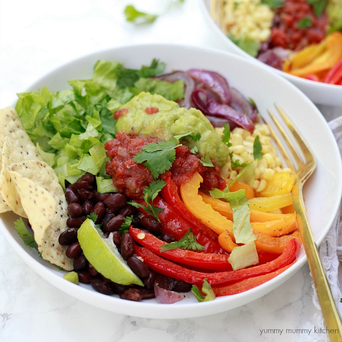 A bowl meal with colorful roasted fajita vegetables, quinoa, guacamole, salsa, lettuce, and chips.