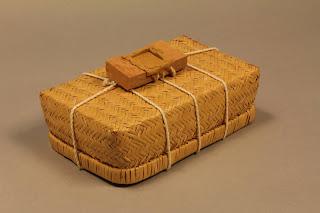 箱に紐をかけ、紐の結び目に粘土のせて印を押した「封泥」