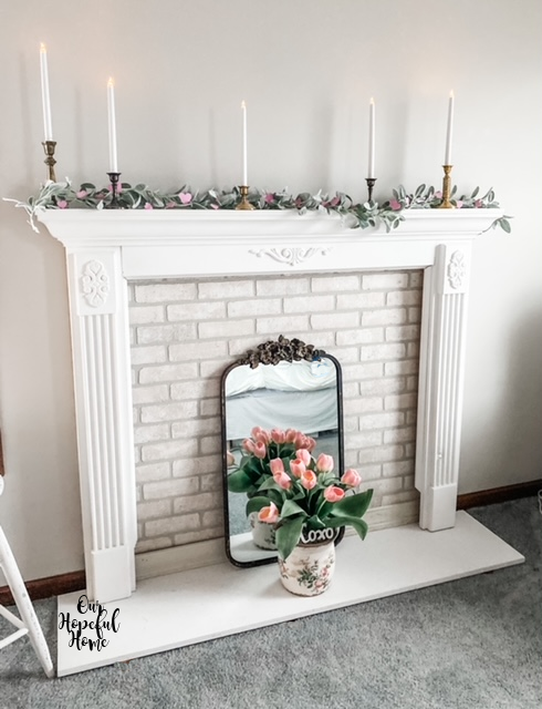 white fireplace mantel white taper candles brass candlesticks whitewashed brick facade