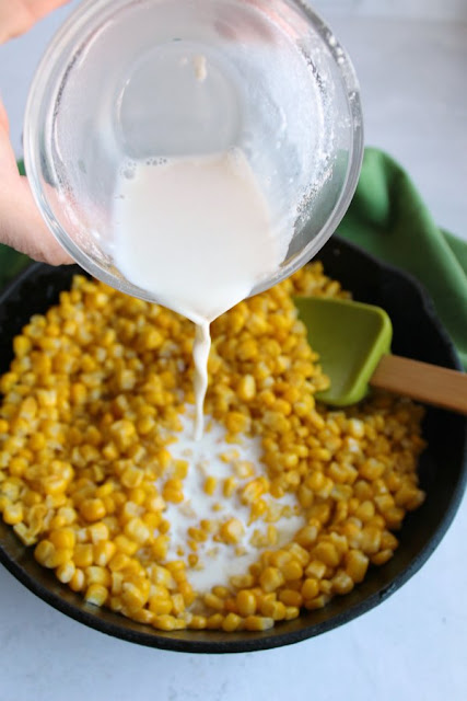 pouring milk mixture over corn in cast iron skillet