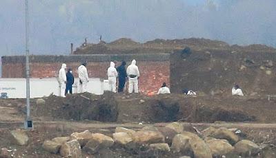 Para pekerja berpakaian hazmat di kuburan massal di pulau Hart, New York