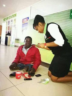 A lady assisting a physical challenged person in Nakuru.