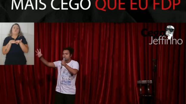 A imagem mostra Jeffinho no palco atuando. No canto esquerdo uma intérprete de libras